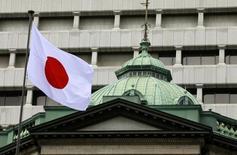 Флаг Японии на здании ЦБ в Токио, 26 сентября 2012 года. Банк Японии сохранил программу стимулов и оставил прогнозный ориентир инфляции на следующий год на уровне 2 процентов, несмотря на недавнюю статистику, бросившую тень сомнений на сценарий банка о восстановлении за счет инвестиций. REUTERS/Yuriko Nakao