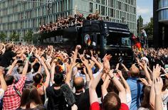 El equipo de fútbol alemán saluda a sus fans desde el bubs que lo llevó a la gran celebración por el triunfo de la Copa del Mundo 2014 en Brasil, 15 de julio de 2014.  Cientos de miles de alemanes recibieron el martes a su triunfante selección de fútbol en Berlín, ondeando banderas y vistiendo los colores nacionales en medio de los festejos por la obtención de su cuarta Copa del Mundo. REUTERS/Morris Mac Matzen