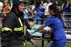Врач скорой помощи везет пострадавшего в аварии в московском метро 15 июля 2014 года. Следствие полагает, что закрепленная тонкой проволокой стрелка в московском метро стала причиной крупнейшей в его истории аварии, которая унесла жизни 21 человека. REUTERS/Sergei Karpukhin