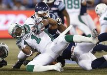 Saskatchewan Roughriders running back Kory Sheets runs the ball against Toronto Argonauts' Armond Armstead (back) during the first half of their CFL football game in Toronto October 8, 2012. REUTERS/Mark Blinch