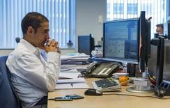 Управляющий менеджер Voya Russia Fund Натан Гриффитс в офисе фонда в Гааге 14 мая 2014 года. EPFR Global зафиксировал чистый отток средств из инвестирующих в Россию фондов за неделю, завершившуюся 16 июля, в размере $96 миллионов, преимущественно - из ETF, пишут аналитики Уралсиб Кэпитал. REUTERS/Michael Kooren