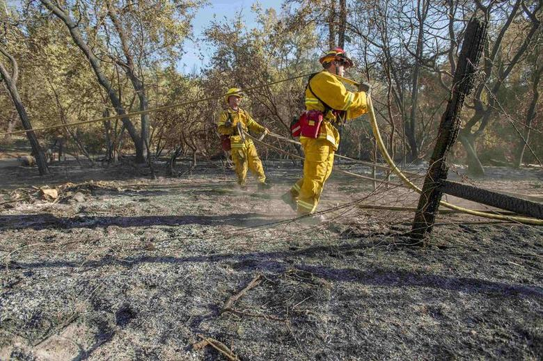 Rohnert Park firefighters pack up hoses after spraying a hot spot of the Butts fire in Snell Valley, California July 3, 2014. The fire has scorched more than 4,300 acres since it started Tuesday.   REUTERS/Noah Berger