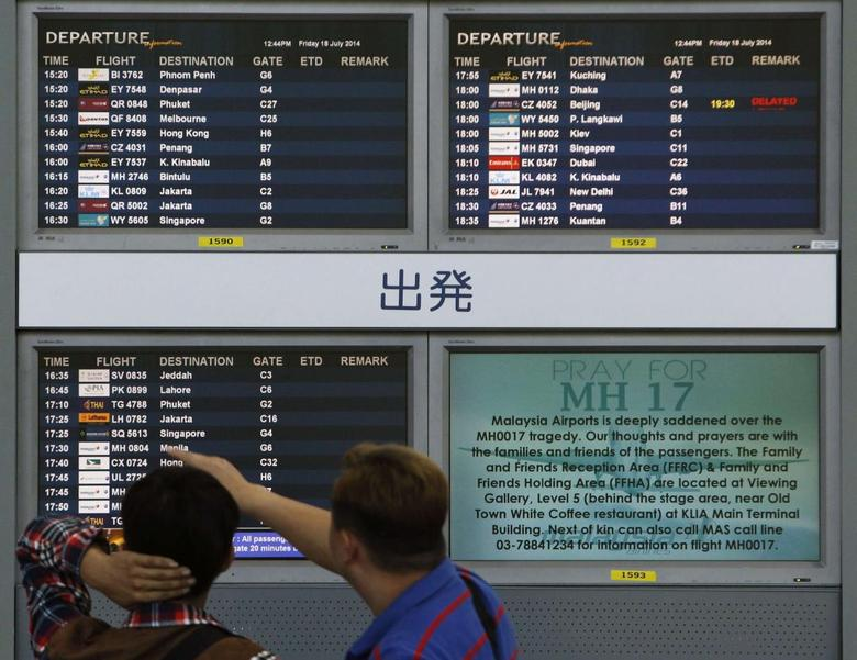 Bystanders look at a board displaying flight information and a ''Pray for MH17'' message at Kuala Lumpur International Airport in Sepang July 18, 2014.  REUTERS/Edgar Su
