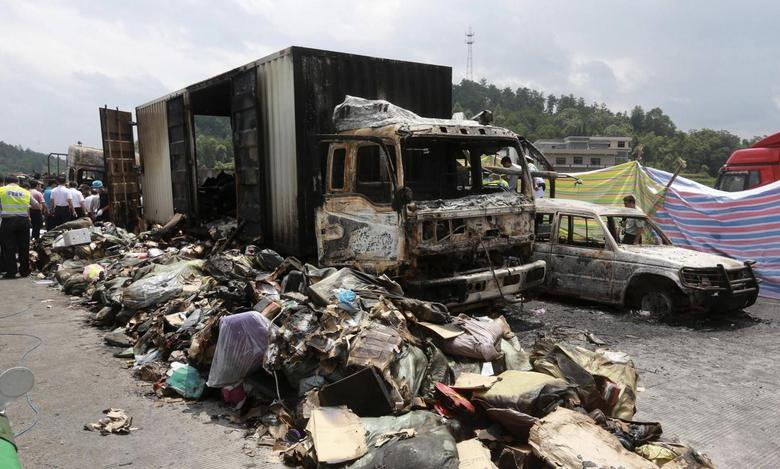 Debris is seen next to burnt vehicles after an explosion and a fire following a traffic accident, at a section of the Hukun (Shanghai to Kunming) highway in Shaoyang, Hunan province July 19, 2014. REUTERS/China Daily