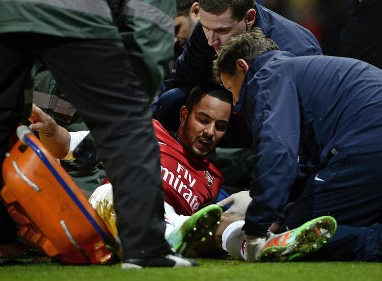 Arsenal's Theo Walcott holds shows his agony as he is injured during their English FA Cup soccer match against Tottenham Hotspur at the Emirates stadium in London, January 4, 2014.  REUTERS/Dylan Martinez