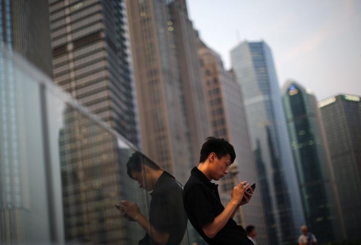 A man looks at the screen of his mobile phone at Pudong financial district in Shanghai July 8, 2013. REUTERS/Carlos Barria