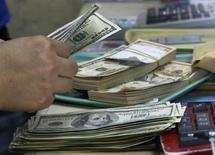 Imagen de archivo de un empleado contando dólares en una casa de cambios en Manila, sep 19 2013. El dólar estadounidense cerró estable frente a una cesta de importantes monedas el lunes, en momentos en que inversores reducían sus tenencias de acciones y otros activos de riesgo ante la ansiedad por la escalada de la violencia en Gaza y Ucrania.  REUTERS/Romeo Ranoco