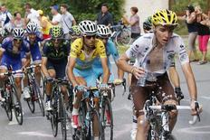 The pack of riders including Romain Bardet (R) of France and race leader Astana team rider Vincenzo Nibali (2ndR) of Italy cycles on its way in the Alps Mountains during the 177-km fourteenth stage of the Tour de France cycling race between Grenoble and Risoul, July 19, 2014.  REUTERS/Jean-Paul Pelissier