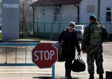 """КПП """"Успенка"""" на российско-украинской границе 25 марта 2014 года. Европейский союз пригрозил России новыми санкциями, включая экономические, если она будет препятствовать расследованию крушения малайзийского лайнера на Украине и помогать повстанцам, но для введения новых ограничений Европе придется пройти долгий путь согласований. REUTERS/Yannis Behrakis"""