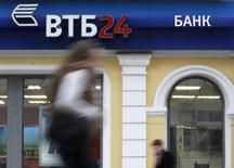 """Отделение ВТБ 24 в Москве 3 апреля 2013 года. Девальвация и торможение экономики всё чаще вынуждают беднеющих россиян идти в банк за деньгами, а не с деньгами, и российский рынок вкладов физлиц в лучшем случае вырастет на 6-7 процентов в текущем году, а население продолжит больше занимать, чем сберегать, считает глава розничной """"дочки"""" второго по величине госбанка ВТБ 24 Михаил Задорнов. REUTERS/Sergei Karpukhin"""