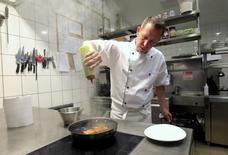 Chef Akos Sarkozi prepares food in the kitchen of the Borkonyha (Wine Kitchen) restaurant in Budapest, June 17, 2014.REUTERS/Bernadett Szabo