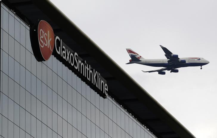 A British Airways airplane flies past a signage for pharmaceutical giant GlaxoSmithKline (GSK) in London April 22, 2014.  REUTERS/Luke MacGregor