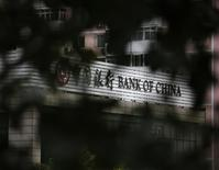 Bank of China's logo is seen through trees at its branch office in Beijing July 14, 2014. REUTERS/Kim Kyung-Hoon