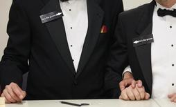 """Two men, both wearing signs that read """"he's the groom"""", hold hands shortly after midnight after getting a civil union when Colorado's civil union law went into effect in Denver May 1, 2013. REUTERS/Rick Wilking"""