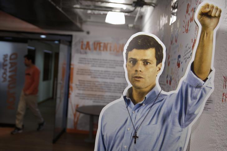A man walks behind a cardboard figure of jailed opposition leader Leopoldo Lopez at the headquarters of political party Popular Will (Voluntad Popular) in Caracas June 5, 2014. REUTERS/Carlos Garcia Rawlins/Files