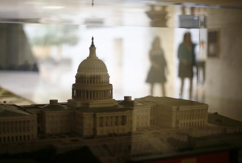 Staffers in the Dirksen Senate building walk past a scale model of the U.S. Capitol in Washington October 7, 2013.  REUTERS/Jason Reed