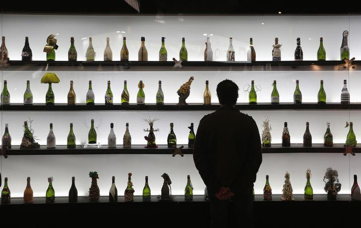 A visitor looks bottles of cava (sparkling wine) on a display at the Alimentaria trade show in Barcelona April 2, 2014. REUTERS/Albert Gea/Files