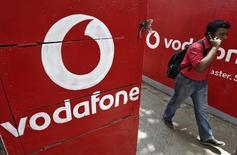 En la imagen, un hombre habla por su teléfono celular junto a una publicidad de Vodafone en Kolkata, India, el 20 de mayo de 2014. Vodafone reportó otra gran caída trimestral en su principal medida de ingresos, debido a que la debilidad en Sudáfrica y España neutralizó la estabilización en el resto de Europa, y la firma dijo que no se espera hasta fines de año una mejora más amplia. REUTERS/Rupak De Chowdhuri