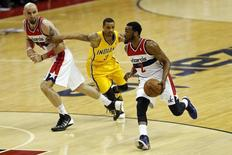 Washington Wizards guard John Wall (2) dribbles the ball past Indiana Pacers guard George Hill (3) and Wizards center Marcin Gortat (4) in the first quarter in game six of the second round of the 2014 NBA Playoffs at Verizon Center. May 15, 2014; Washington, DC, USA; Geoff Burke-USA TODAY Sports