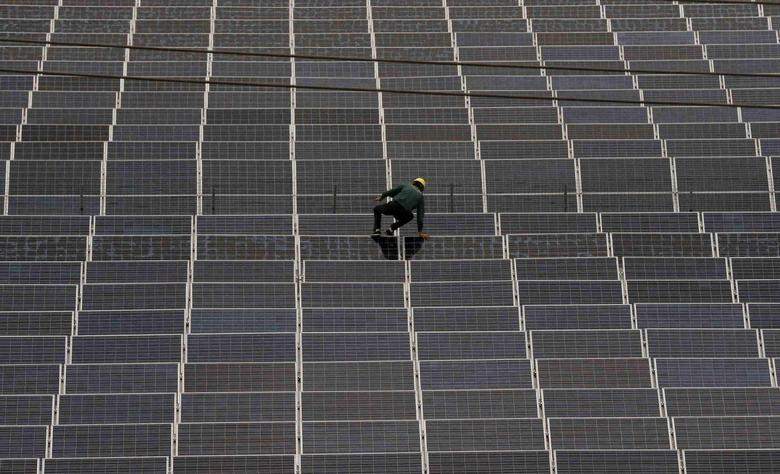 A worker climbs over a solar panel at a solar factory in Longyou county, Zhejiang province, June 24, 2014.  REUTERS/William Hong