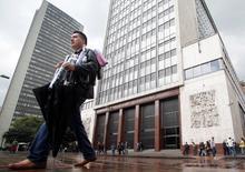 Imagen de archivo de un hombre a las afueras del Banco Central colombiano en Bogotá, mar 1 2011. El presupuesto de gastos de Colombia del 2015 rondaría unos 220 billones de pesos (119.000 millones de dólares), equivalente a un incremento de 8,5 por ciento, dijo el lunes el ministro de Hacienda, Mauricio Cárdenas. REUTERS/John Vizcaino