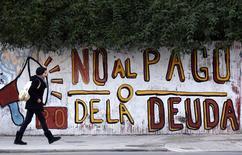 """Una mujer pasa junto a un mural alusivo a los pagos de deuda incumplidos por Argentina en Buenos Aires, jul 28 2014. Argentina ha enfrentado en los tribunales por algo más de una década los reclamos de los inversores """"holdouts"""" por su deuda incumplida, y el país sudamericano ha perdido.    REUTERS/Marcos Brindicci"""
