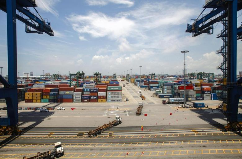 Containers are transported at Nansha port in Guangzhou, Guangdong province, June 26, 2014. REUTERS/Alex Lee
