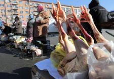 Люди торгуют на рынке в Киеве 3 февраля 2014 года. Россия готовится ввести пошлины на более чем сотню наименований товаров с Украины, включая сельхозпродукцию, металлы и машины, после подписания Киевом соглашения с ЕС и на фоне конфликта между двумя странами, который привел к введению санкций против РФ. REUTERS/Konstantin Chernichkin
