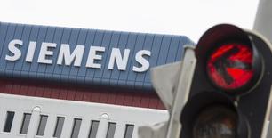 Логотип Siemens AG на фоне светофора в Мюнхене 30 мая 2014 года. Немецкий концерн Siemens AG предупредил о возможных сложностях, которые могут ждать в будущем энергетическое подразделение, также отчитавшись о не оправдавшей ожидания аналитиков прибыли в третьем квартале финансового года. REUTERS/Lukas Barth