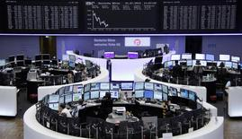 Traders are pictured at their desks in front of the DAX board at the Frankfurt stock exchange July 31, 2014.      REUTERS/Stringer/Remote
