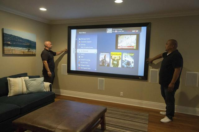 Alex Vybourg (L) and Will Luzadas of audio visual integration company SpeakerGuy Inc. look at a projector screen they installed in a home in Manhattan Beach, California July 29, 2014.  REUTERS/Lucy Nicholson