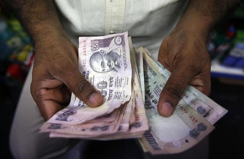 A private money trader counts rupee currency notes at a shop in Mumbai August 1, 2013. REUTERS/Vivek Prakash/Files