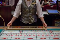 A croupier sits in front of a gaming table inside a casino on the opening day of Sheraton Macao hotel at Sands Cotai Central in Macau in this September 20, 2012 file photo.  REUTERS/Tyrone Siu/Files