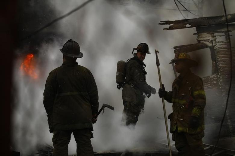 Detroit firefighters try to contain a fire at a shed in Detroit, Michigan December 3, 2013.  REUTERS/Joshua Lott