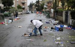 Мужчина собирает продукты после завершения работы уличного рынка в Риме 10 декабря 2012 года. Экономика Италии неожиданно вновь скатилась в рецессию во втором квартале 2014 года: ВВП страны сократился на 0,2 процента по сравнению с предыдущим кварталом, свидетельствуют предварительные данные ISTAT. REUTERS/Max Rossi