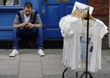 A man uses his mobile phone next to a rail of clothes for sale in central London August 10, 2013.  REUTERS/Luke MacGregor