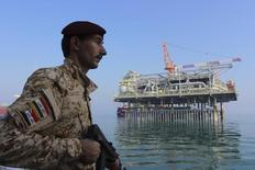 Иракский солдат охраняет нефтяную платформу в Персидском заливе 27 ноября 2013 года. Нефть Brent подорожала в пятницу после того, как США одобрили авиаудары по исламистским боевикам на севере Ирака, подстегнув опасения о поставках нефти из второго крупнейшего производителя ОПЕК. REUTERS/Essam Al-Sudani