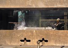An employee works with a titanium ingot at the VSMPO-Avisma factory in Verkhnyaya-Salda, some 1,800 km (1,100 miles) east of Moscow, in this November 7, 2013 file photo.   REUTERS/Svetlana Burmistrova/Files