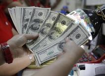 Un empleado cuenta dólares al interior de una casa de cambios en Manila, abr 1 2013. El yen y el franco suizo subían el viernes, pues los inversores buscaban la relativa seguridad de esas monedas después de otra escalada en las tensiones geopolíticas luego de que Estados Unidos lanzara un ataque aéreo contra Irak por primera vez desde que las tropas estadounidenses salieron del país en el 2011. REUTERS/Romeo Ranoco