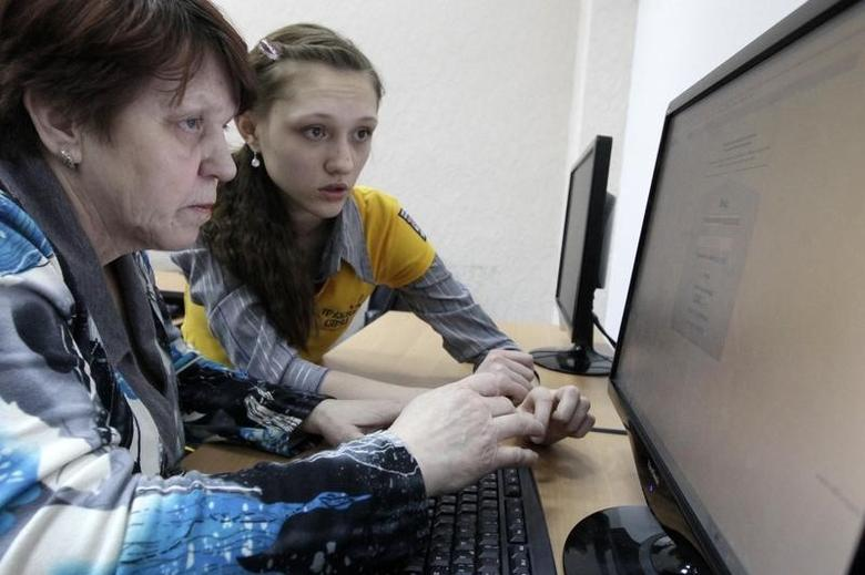 A pensioner listens to a young instructor during a free lesson on using the Internet at a youth club in Russia's Siberian city of Krasnoyarsk, February 11, 2013. REUTERS/Ilya Naymushin/Files