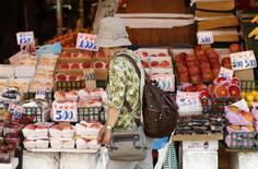 Mulher observa frutas em uma área comercial em Tóquio, no Japão, em julho. 29/07/2014 REUTERS/Yuya Shino