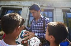 Atacante Uruguaio Suárez concede autógrafos após audiência na CAS, em Lausanne. 08/08/2014 REUTERS/Denis Balibouse