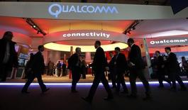 Visitors walk past the Qualcomm stand at the Mobile World Congress in Barcelona, February 24, 2014. REUTERS/Albert Gea