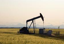 Станок-качалка на месторождении нефти близ Калгари, провинция Альберта 21 июля 2014 года. Brent упала ниже $104 за баррель в четверг на фоне избыточных поставок и опасений по поводу слабого спроса, несмотря на продолжающиеся кризисы в Ираке и на Украине. REUTERS/Todd Korol