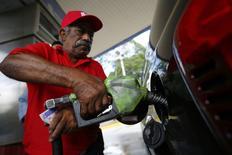 Imagen de archivo de un empleado cargando combustible en una gasolinera de Caracas, ago 7 2014. La cesta venezolana de crudos y derivados retrocedió por tercera semana consecutiva al perder 0,27 dólares por barril (dpb), afectada por una menor demanda global en medio de amplios suministros petroleros, dijo el viernes el Ministerio de Petróleo y Minería.  REUTERS/Jorge Silva