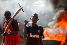 A boy gestures in front of a barricade on fire during a protest after French troops opened fire at protesters blocking a road in Bambari. REUTERS/Goran Tomasevic
