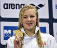 Ruta Meilutyte of Lithuania poses with her gold medal after winning the women's 100m Medley final during the LEN European Short Course Swimming Championship in Herning, December 14, 2013. REUTERS/Henning Bagger/Scanpix Denmark