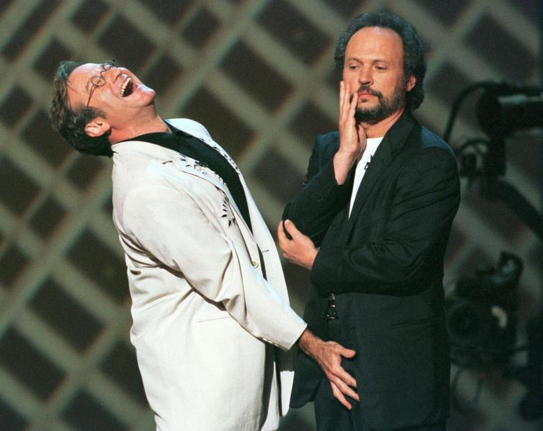 Actor and comedian Robin Williams (L) shares a laugh with actor Billy Crystal on the stage of New York's Radio City Music Hall during HBO's ''Comic Relief 8'' show, June 14, 1998. REUTERS/Jeff Christensen