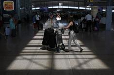 A woman pushes a trolley with suitcases at Barcelona's airport, August 8, 2014. REUTERS/Albert Gea