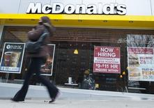A passersby walks in front of a help wanted sign at a McDonalds restaurant in the Brooklyn borough of New York, March 7, 2014.  REUTERS/Keith Bedford